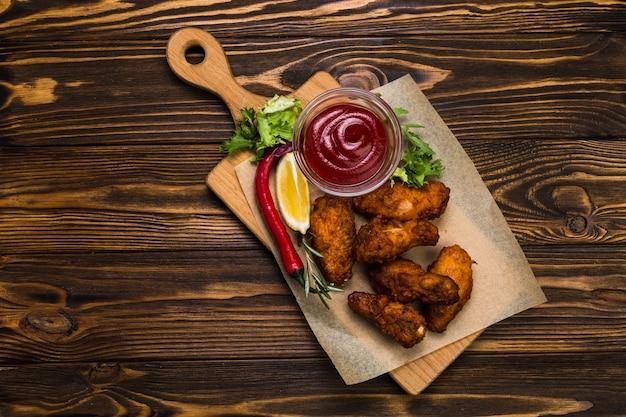Сверху жареная курица возле соуса