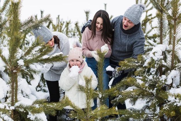 Семья, глядя на девушку, едят снег