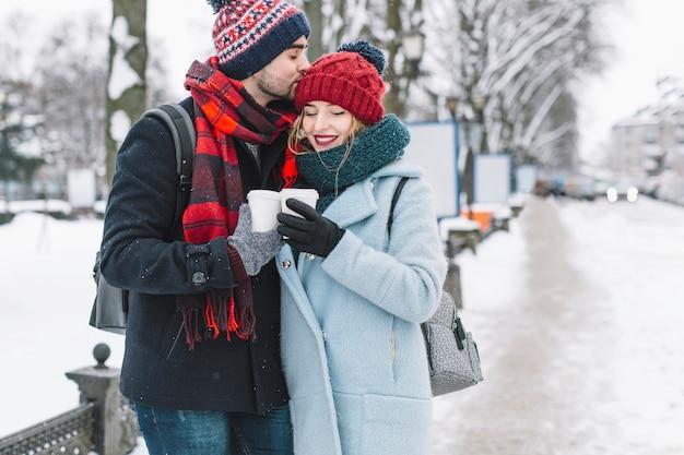 冬にコーヒーを持つ魅力的な若いカップル