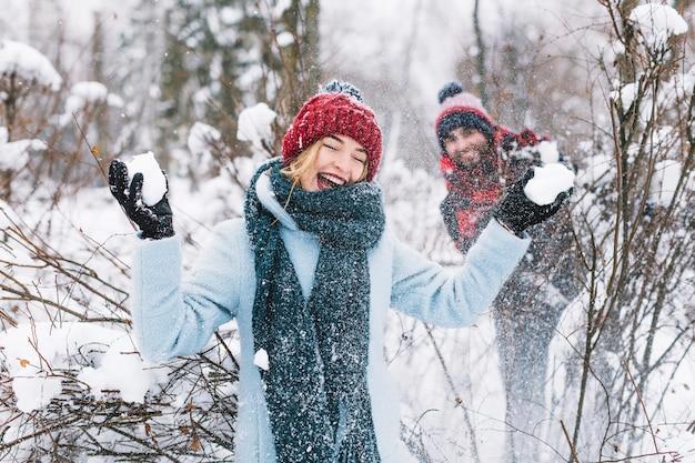 Контент мужчины и женщины, играющие в снежки