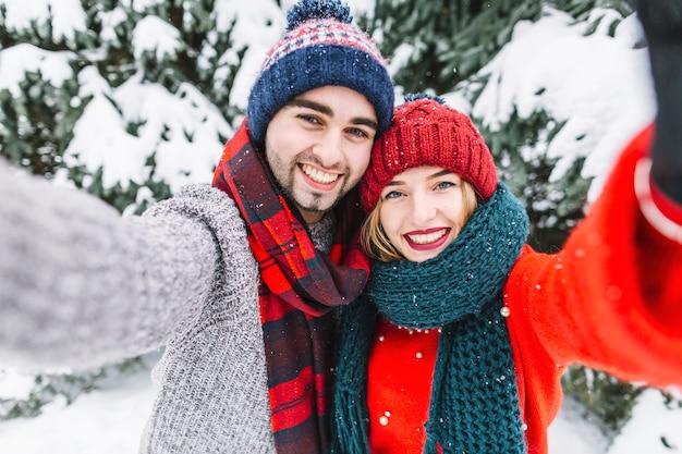 冬にカメラでポーズを取るトレンディなカップル