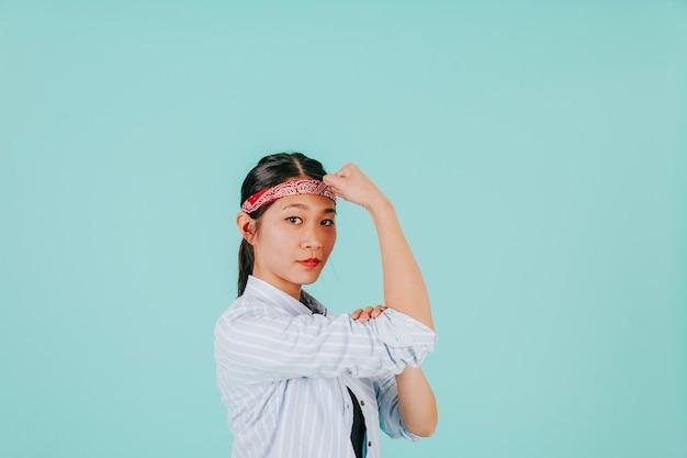 Азиатская женщина показывает бицепс