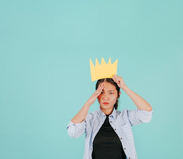 Азиатская женщина в бумажной короне салютует