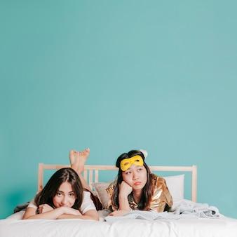 Молодые женщины, лежащие на кровати