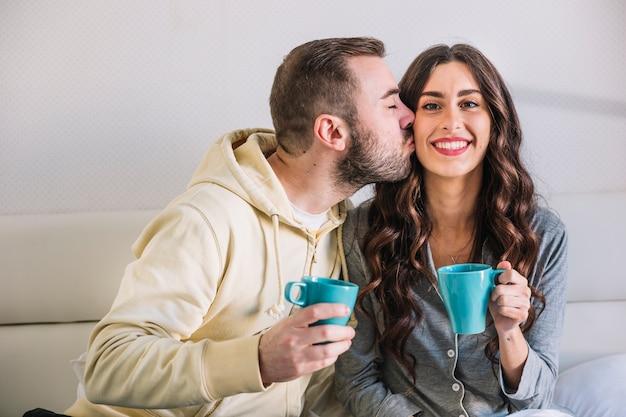 Мужчина целует щеку женщины с чашкой