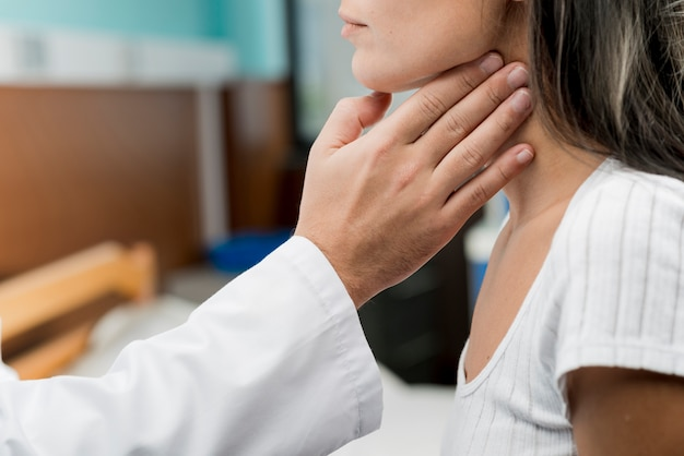 Рука, касающаяся горла пациента
