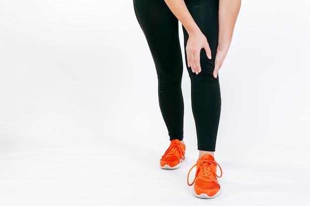 Женщина-обрезка касается больного колена