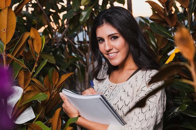 温室でノートを作る笑顔の女性