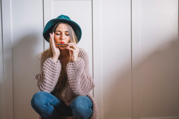 Женщина, играющая на гармонике возле белой стены