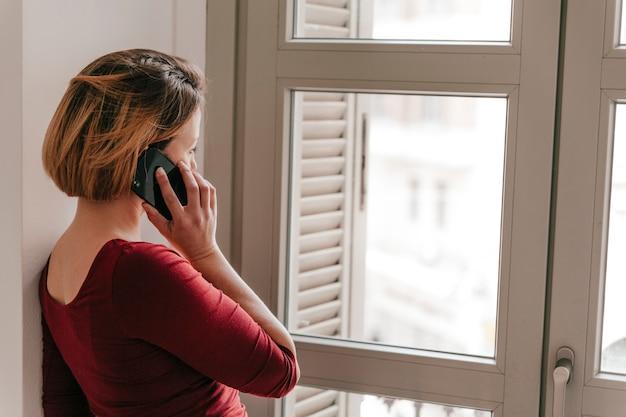 窓の近くのスマートフォンで話す女性