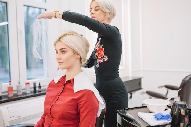 プロシージャのためのクライアントを準備している美容師