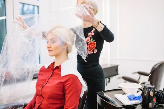 プラスチック製のケープで顧客を保護する美容師