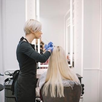 Профессиональный парикмахер, красящий блондинку в кресле