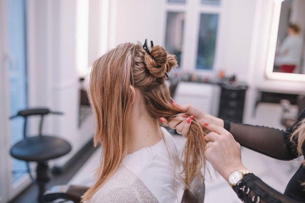 スタイリングのためのクライアントの髪を準備する女性