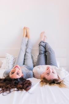 Женщины босиком, лежащие на кровати