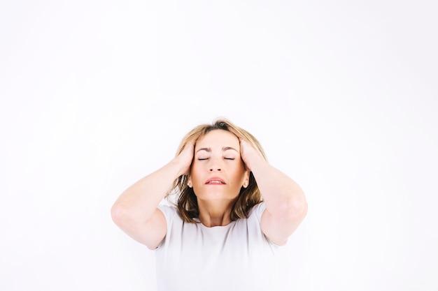 Утомленная женщина, касающаяся головы