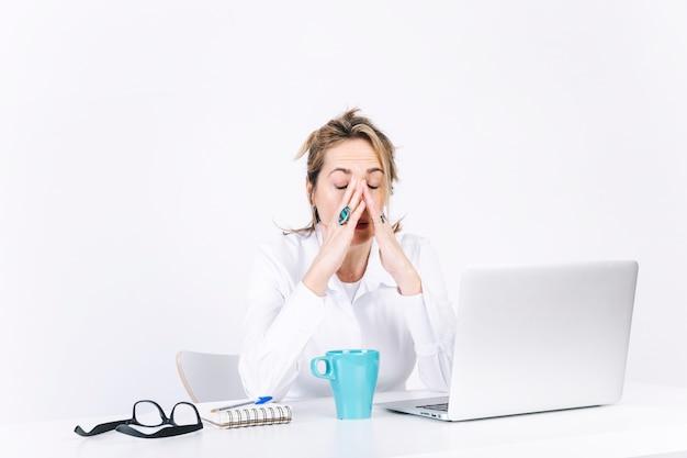 疲れた女性は顔をこすります