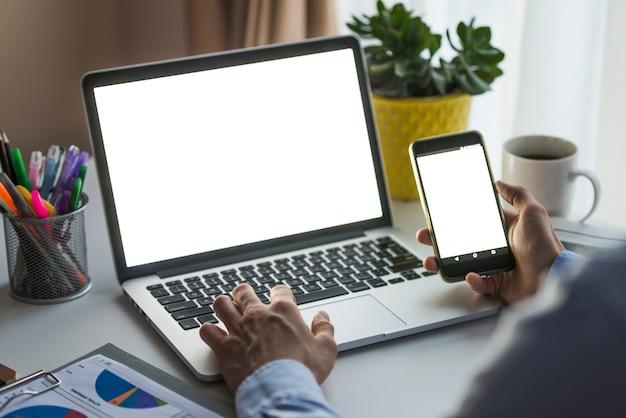 スマートフォンとノートパソコンをオフィスで使用している男