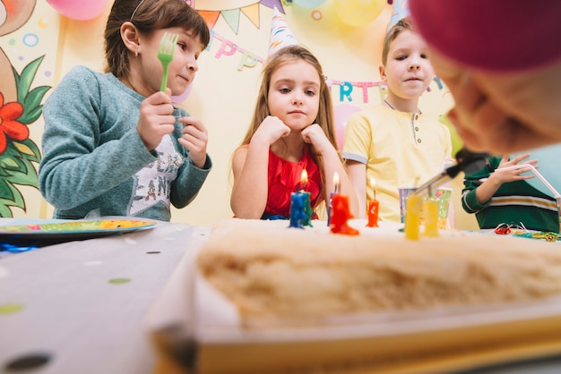 誕生日ケーキを見ている子供たち