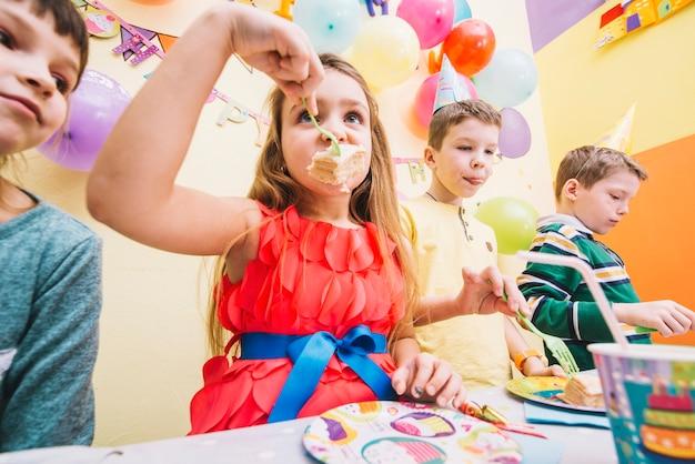 Дети едят вкусный торт ко дню рождения