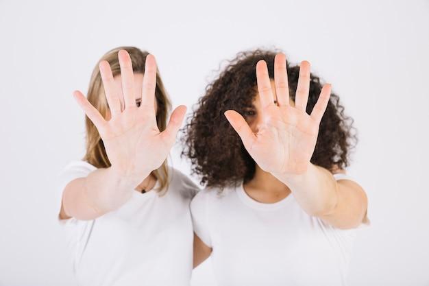 停止のジェスチャーを示す女性