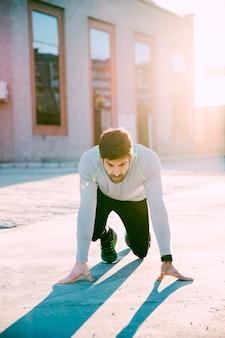 Человек в стартовой позиции перед спринтом