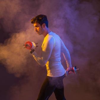 Мужчина-спортсмен позирует с гантелями