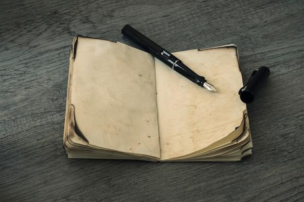 開いた古いノートブックのインクペン