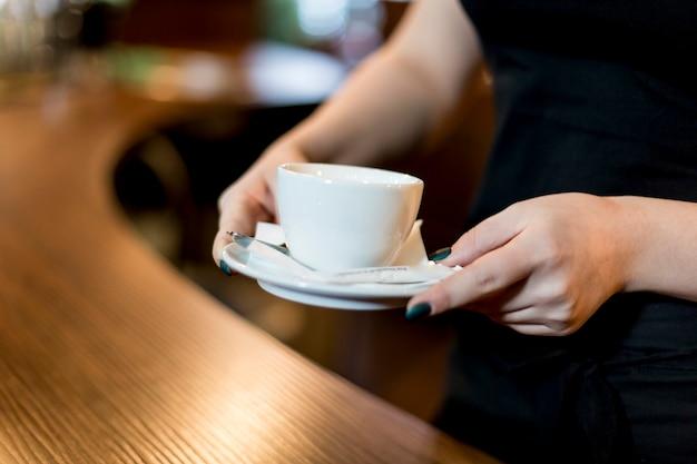 熱い飲み物のカップを持つ作物の女性