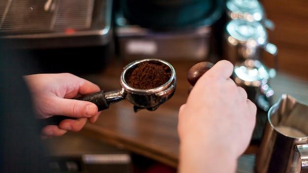 新鮮なコーヒーでポルタフィルターを握る作物の手