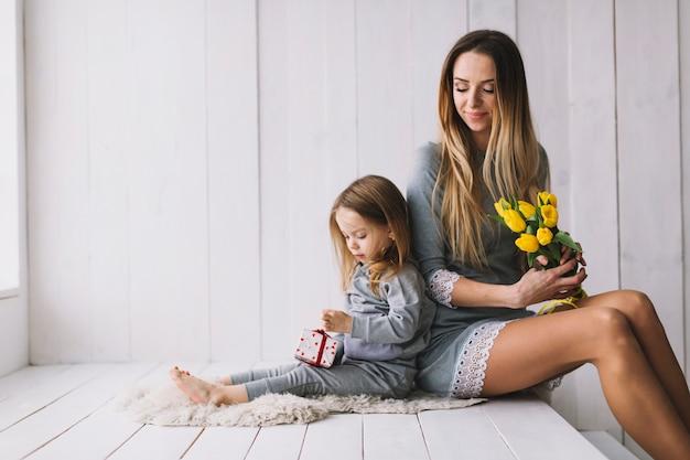 Концепция матери с матерью и дочерью на кровати