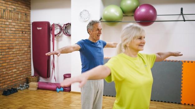 Пожилые люди тренируются в тренажерном зале