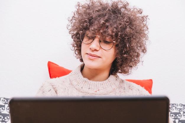 Подросток в очках с помощью ноутбука