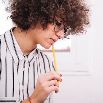 鉛筆で思慮深いティーンエイジャー