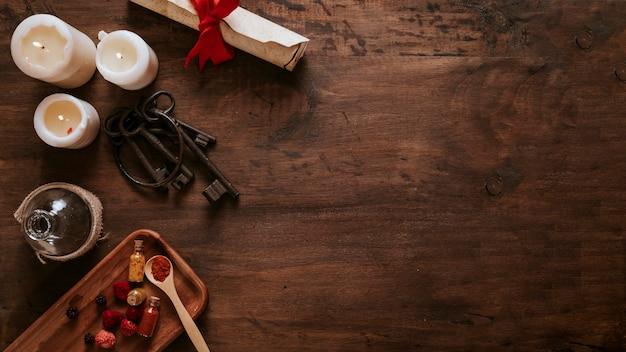 ろうそくの近くのキーと木製テーブルの材料