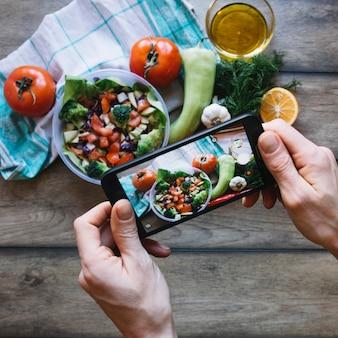 サラダの写真を撮る作物の手