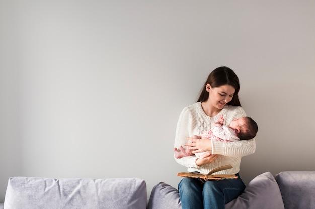 小さな赤ちゃんを持っている本を持つ女性