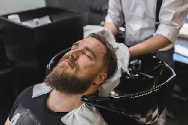 Урожай парикмахера, вытирающего волосы клиента