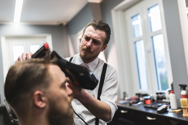 クライアントの髪を乾燥させる美容師