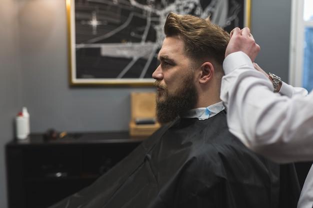 Боковой вид парикмахера, стрижка волос клиента