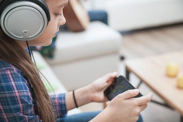 Девушка в наушниках, играющая в игры на смартфоне