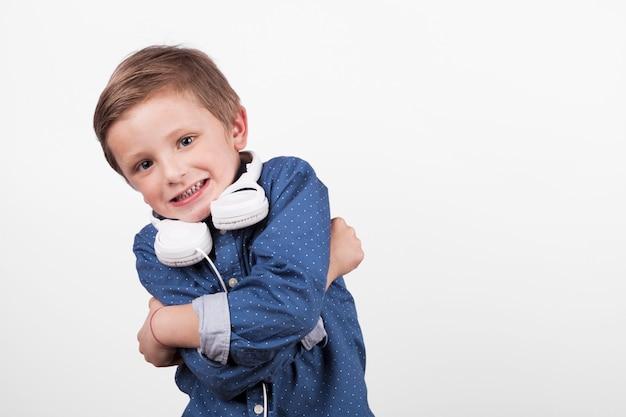 Мальчик с наушниками, обнимающий себя