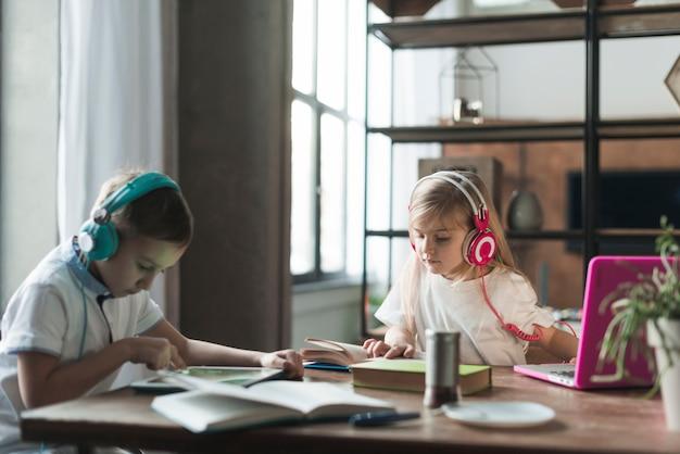 ラップトップと本を持つテーブルの子供たち