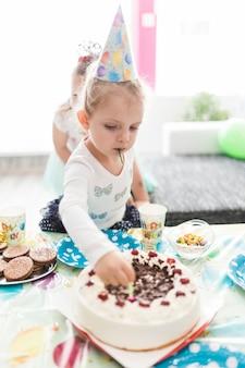 Симпатичная девушка, вынимая свечи из торта