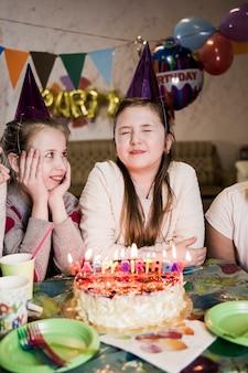 女の子は誕生日パーティーで願い事を作る