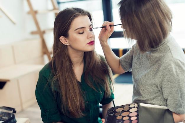 Художник-макияж, применяющий тени для век на модели