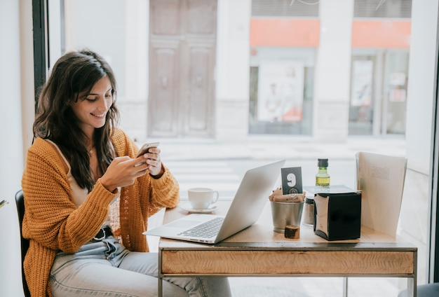 Веселая женщина, просматривающая смартфон в кафе