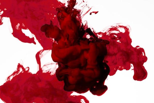 Поток ярких красных чернил под водой