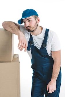 箱の近くに疲れたデリバリーマン