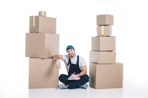 小包の積み重ね間のクリップボードを持つ宅配便